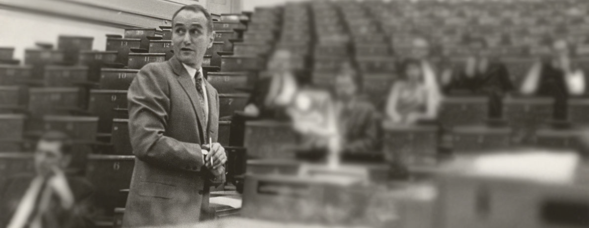 Professor Daniel M. Stressguth (1924-2020) in an old black and white photo standing at the front of a lecture hall with blurred people in the background