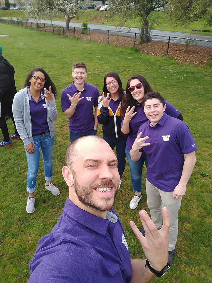 Team members pose for a photo with their hands in the shape of a W for UW.