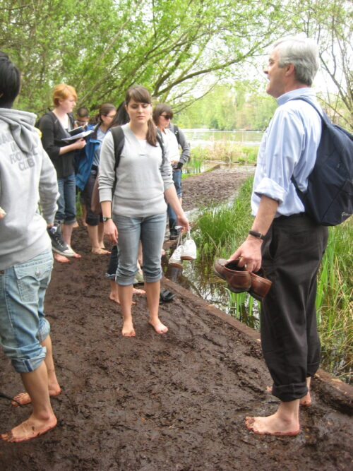 Iain and students in a park barefoot standing in mud