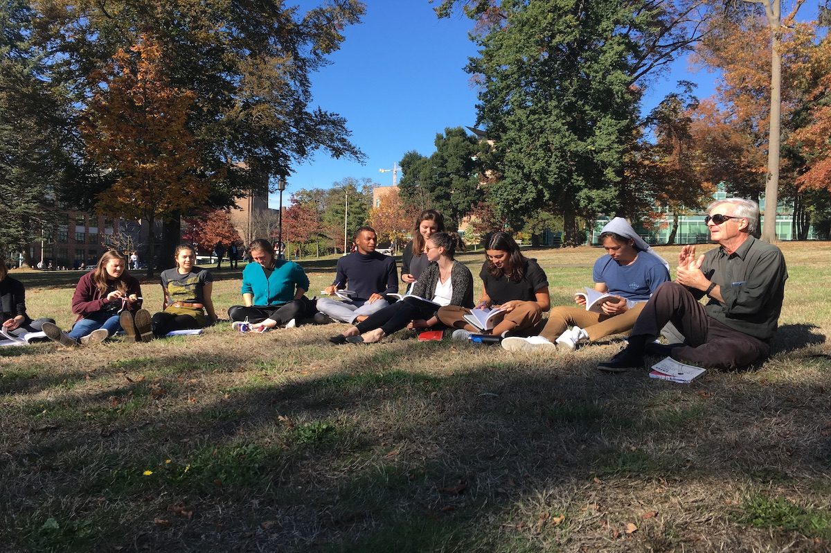 Iain sitting in the grass with a group of students
