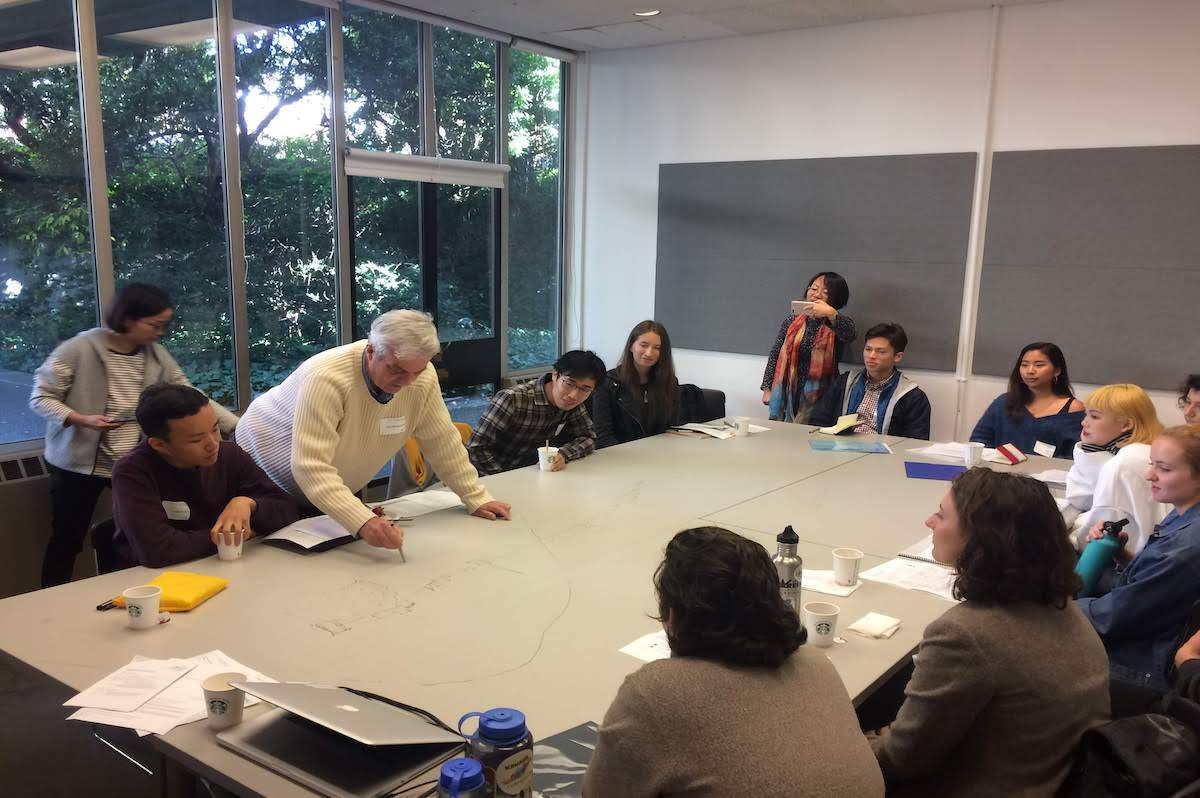 Iain with a group of students drawing on the table